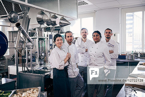 Portrait of chefs standing together in commercial kitchen