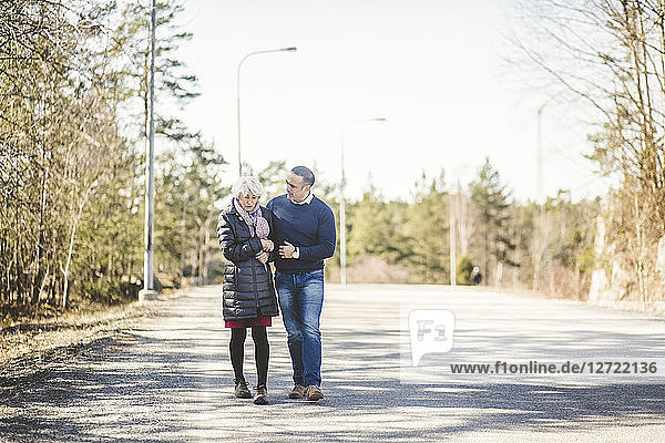 Full length of senior woman walking arm in arm with son on road