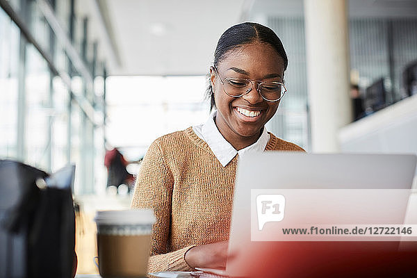 Smiling young female student using laptop while studying at table in university cafeteria
