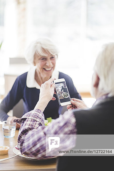 Senior man holding mobile phone while sitting with cheerful woman at table in nursing home