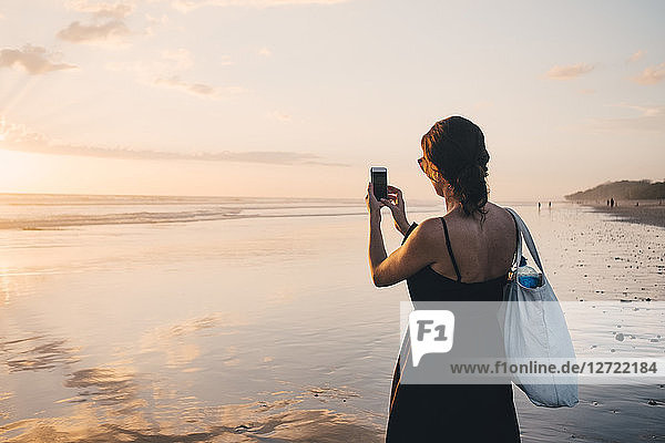 Rear view of woman photographing sunset over sea using mobile phone at beach