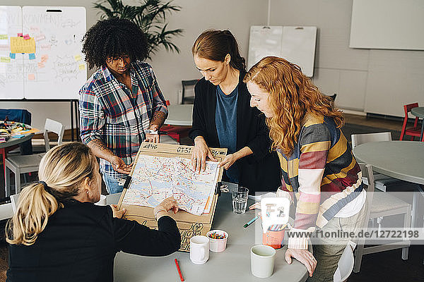 Multi-ethnic students showing map on placard to female manager at table in creative office