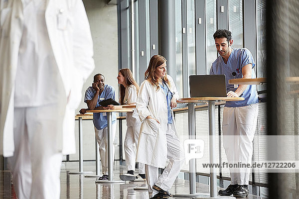 Young nurse discussing with mid adult doctor over laptop while standing against window at hospital