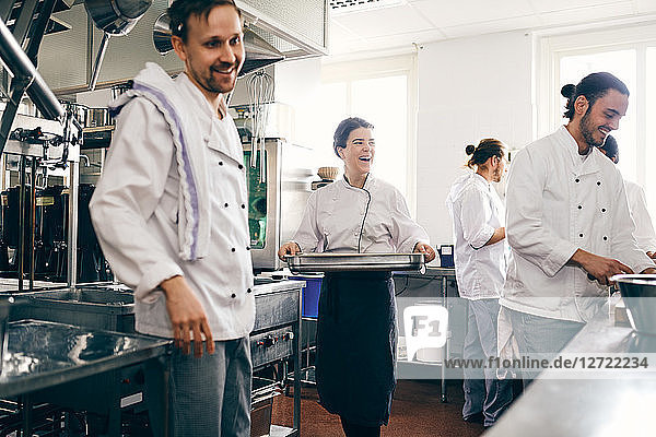 Smiling female chef with colleagues working in commercial kitchen