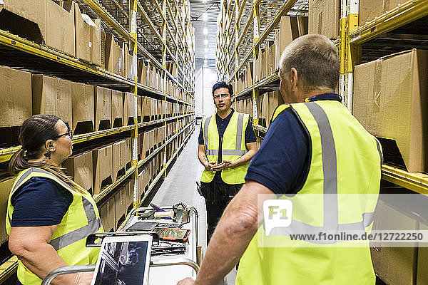 Multi-ethnic coworkers discussing while standing amidst racks at distribution warehouse
