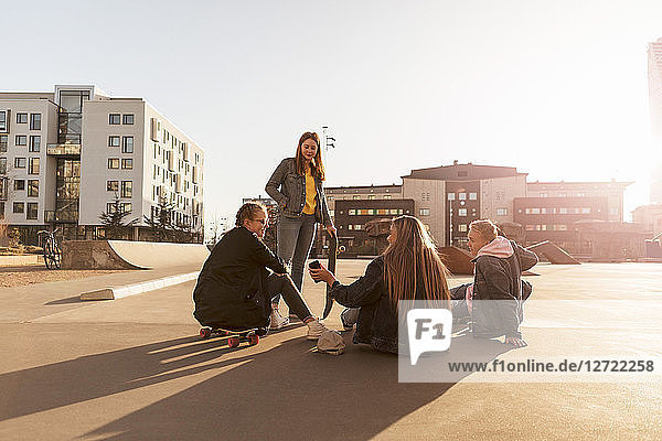 Friends looking at teenager showing mobile phone to girl sitting on skateboard in city