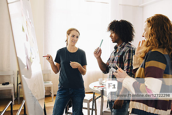 Confident businesswoman discussing project over whiteboard with technicians at creative office