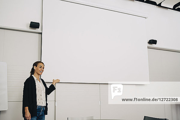 Smiling businesswoman giving presentation over blank projection screen at creative office