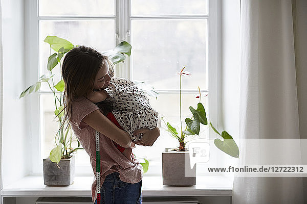 Side view of fashion designer embracing daughter while standing at home