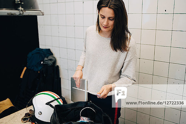 Young busineswoman removing laptop from bag while standing against wall at small office