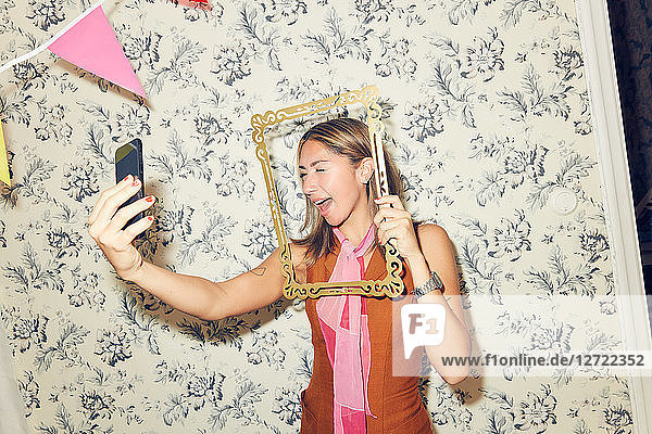Cheerful young woman taking selfie through picture frame while winking at smart phone against wallpaper during party in