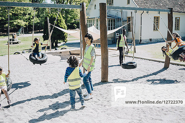 Teachers standing while students enjoying on swing in playground
