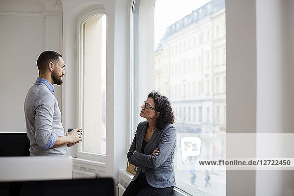 Male and female business colleagues discussing at office