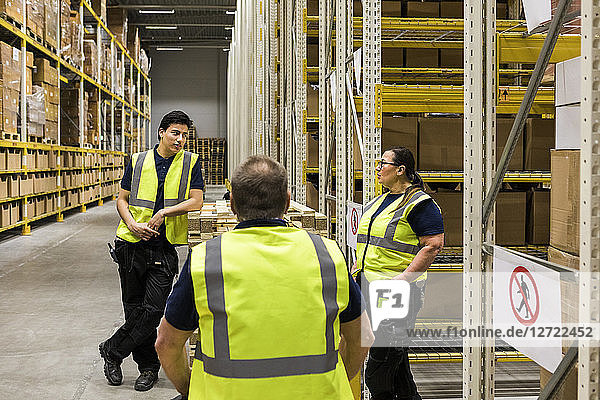 Multi-ethnic coworkers discussing while standing by racks at distribution warehouse