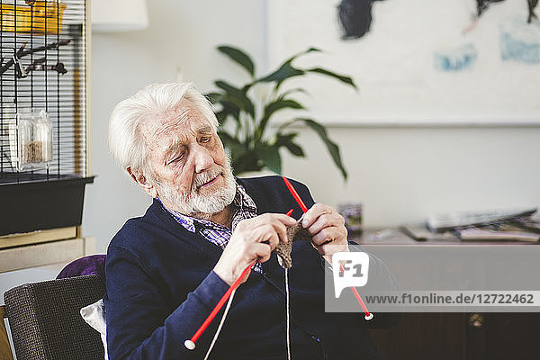 Senior man knitting while sitting in nursing home