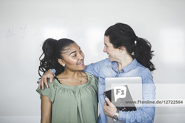 Smiling teenage high school student looking at teacher standing against whiteboard in computer lab