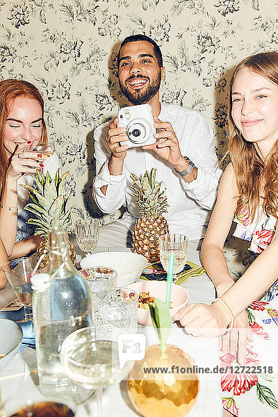 Smiling young man holding camera while sitting amidst female friends at home during dinner party