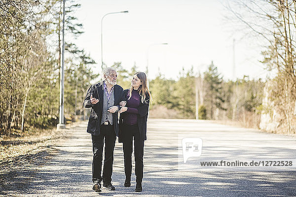 Full length of young woman walking arm in arm with grandfather on road