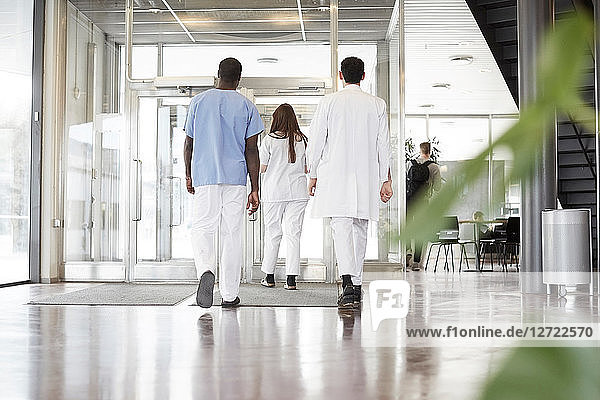 Full length rear view of healthcare workers walking in lobby at hospital