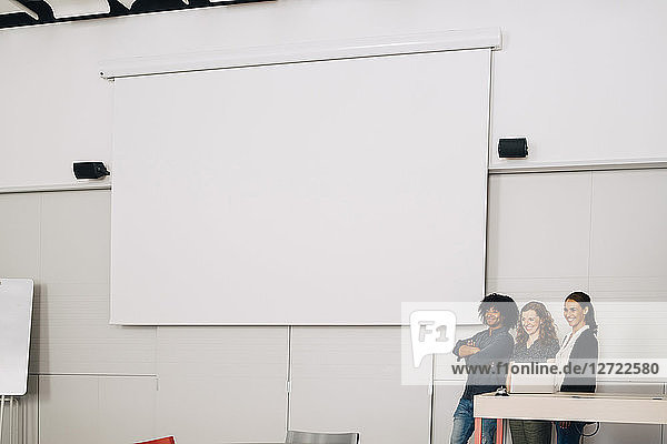 Smiling multi-ethnic technicians standing by blank projection screen at creative office