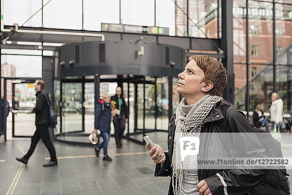 Thoughtful woman holding smart phone while looking up by building in city