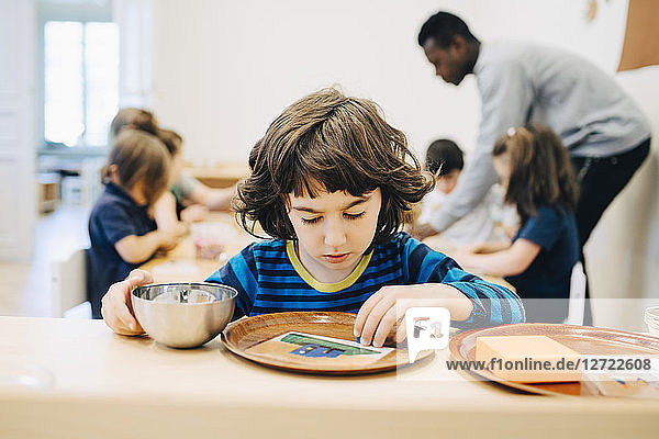 Boy looking at plate on table against friends and teacher in classroom