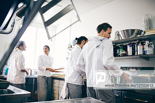 Chefs preparing food at counter in commercial kitchen