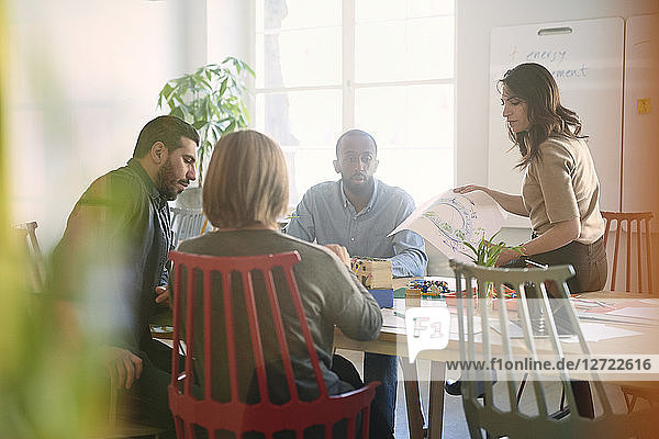 Multi-ethnic male and female engineers are working on project at table in office