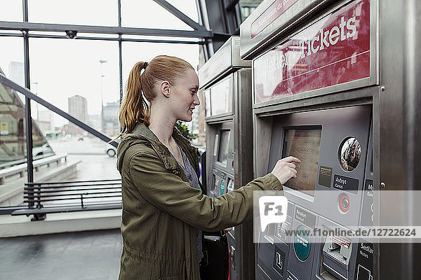 Side view of woman using ticket machine at railroad station