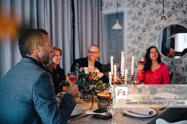 Mature friends enjoying dinner party at home