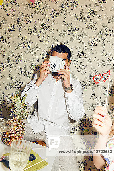Young man photographing while sitting during dinner party at home