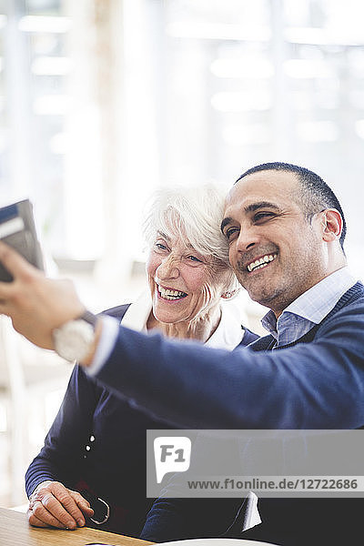 Cheerful mature man taking selfie with mother while sitting at table in nursing home