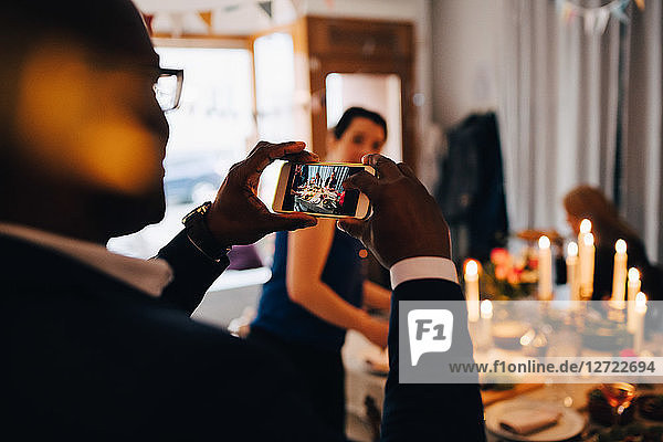 Man photographing friends through smart phone at dinner party