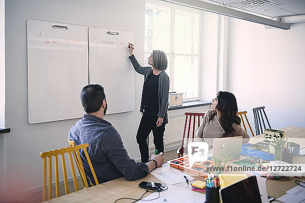 Female engineer writing on whiteboard while explaining colleagues sitting at table in office