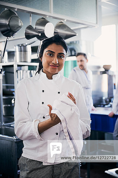 Portrait of confident female chef wiping her hands with napkin in kitchen