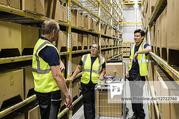 Multi-ethnic coworkers discussing while standing with cart on aisle amidst racks at distribution warehouse