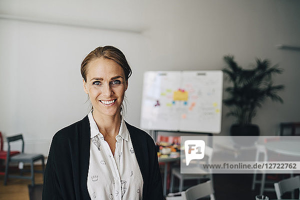 Portrait of smiling mid adult businesswoman standing at creative office