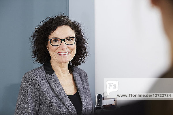 Portrait of smiling confident businesswoman wearing eyeglasses at office
