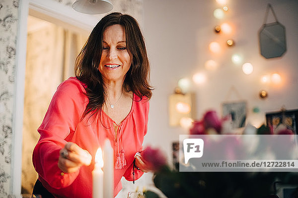 Happy mature woman igniting candle in party at home