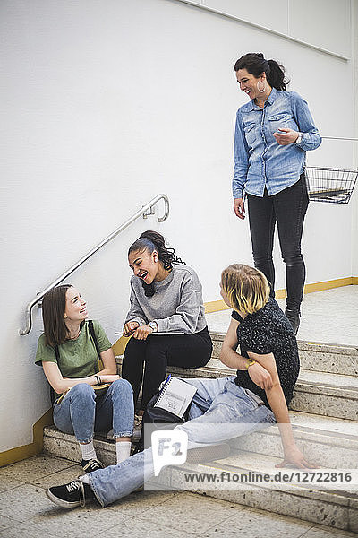 Smiling teacher looking at students sitting on steps at high school