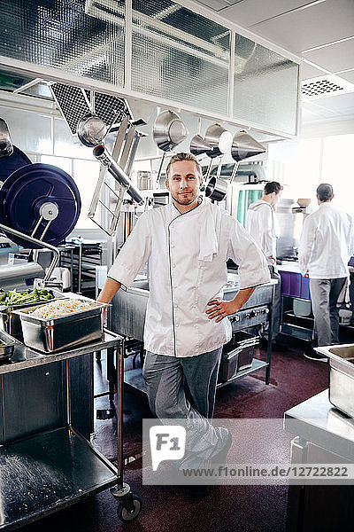Portrait of confident male chef standing in commercial kitchen