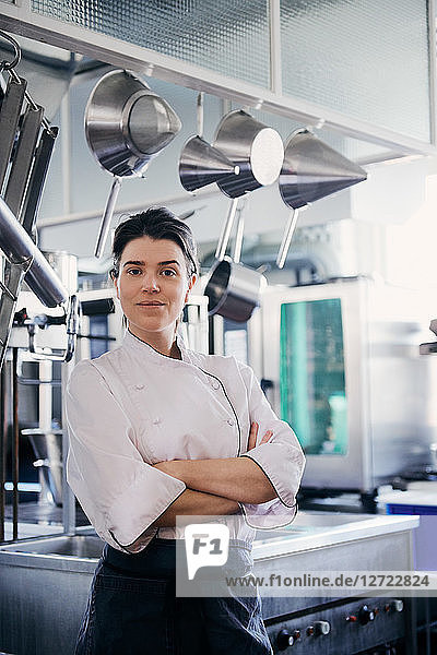 Portrait of mid adult female chef standing arms crossed in commercial kitchen