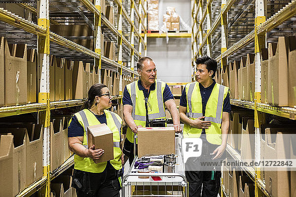Multi-ethnic coworkers discussing while walking with cart on aisle amidst racks at distribution warehouse