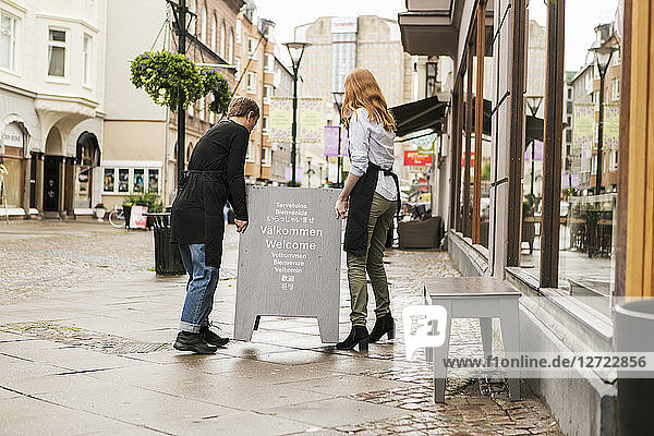 Full length of female owners arranging welcome board outside store in city