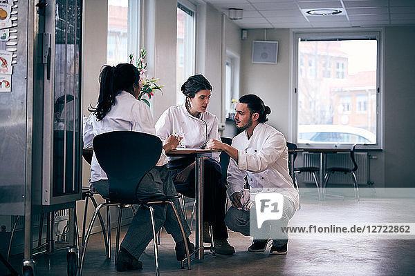 Multi-ethnic chefs discussing menu in restaurant