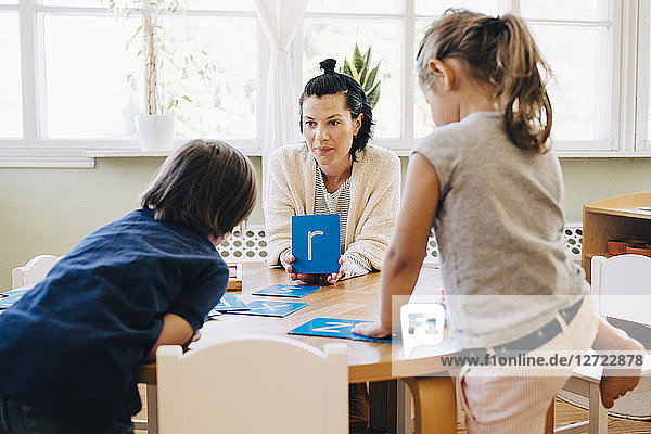 Confident female teacher holding letter R in front of students at table in classroom