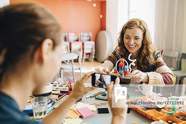 Businesswoman photographing smiling female colleague holding toy at table in creative office