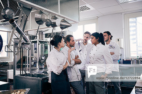 Chefs communicating in commercial kitchen