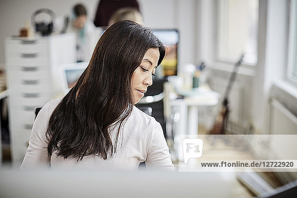 Mature businesswoman looking down while sitting at desk in office