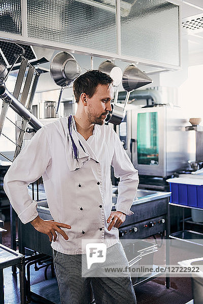 Thoughtful male chef standing with hands on hips in commercial kitchen
